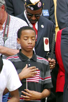 "A boy holds his hands over his heart during ""Taps."""