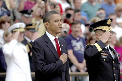 "President Barack Obama places his hand over his heart during the playing of ""Taps."" Standing next to him is Maj. Gen. Richard J. Rowe, Jr. and in the background, wearing white, is Admiral Mike Mullen, Chairman of the Joint Chiefs of Staff."